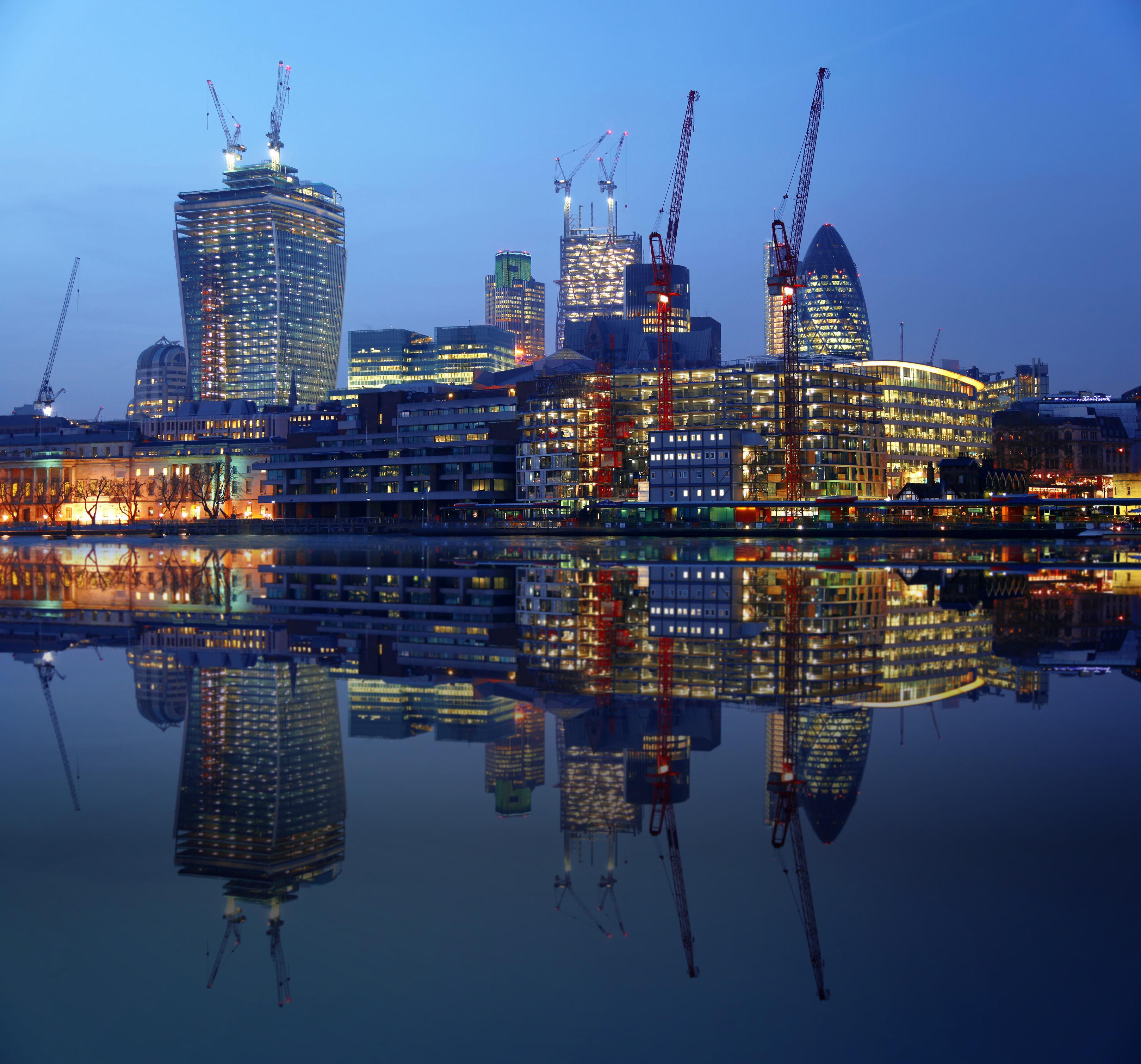 Kvällsbild i London med upplysta byggnader som avspeglas mot vatten.