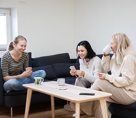 Tre studenter sitter och samtalar med varann