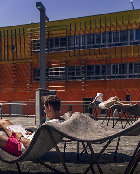 Studenter studerar utomhus halvliggandes i stolar medan solen skiner på dem.