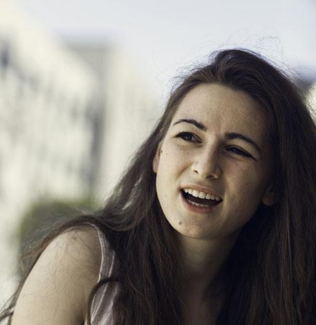 Ung kvinna med mörkt hår säger någonting samtidigt som bilden tas.